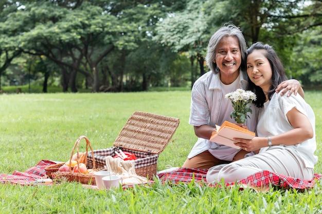 Ältere entspannende paare und picknick am park. frau geben meinem ehemann blume. Premium Fotos