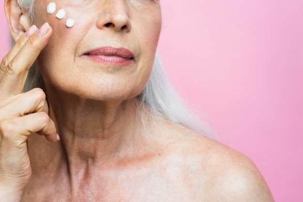 Ältere frau der nahaufnahme, die creme aufträgt Kostenlose Fotos