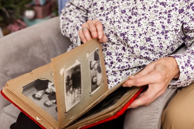 Ältere frau der nahaufnahme, die fotoalbum untersucht Kostenlose Fotos