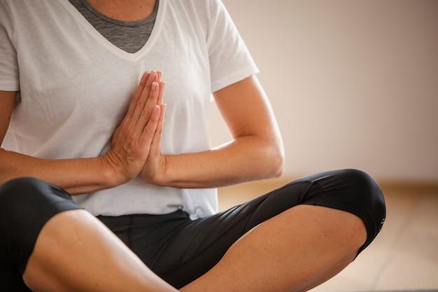 Ältere frau der nahaufnahme, die yoga tut Kostenlose Fotos