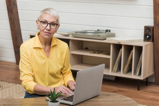Ältere frau der vorderansicht, die durch das internet auf ihrem laptop schaut Kostenlose Fotos