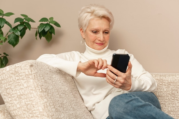 Ältere frau des hohen winkels auf couch unter verwendung des telefons Kostenlose Fotos
