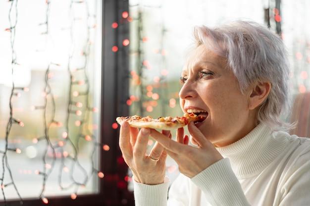 Ältere frau des niedrigen winkels, die pizzascheibe genießt Kostenlose Fotos
