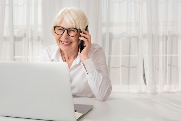 Ältere frau des smiley, die am telefon spricht Kostenlose Fotos