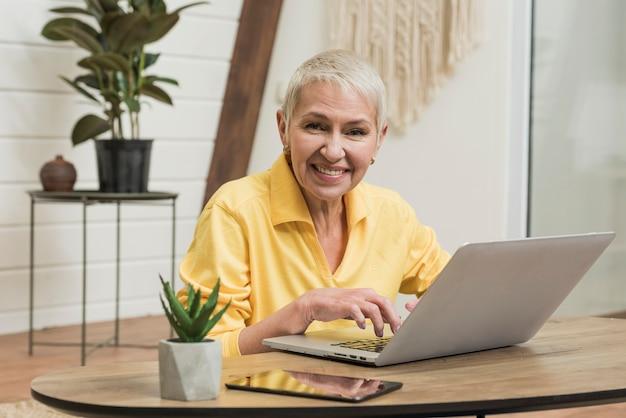 Ältere frau des smiley, die auf ihrem laptop schaut Kostenlose Fotos