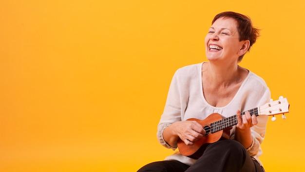 Ältere frau des smiley, die gitarre spielt Kostenlose Fotos