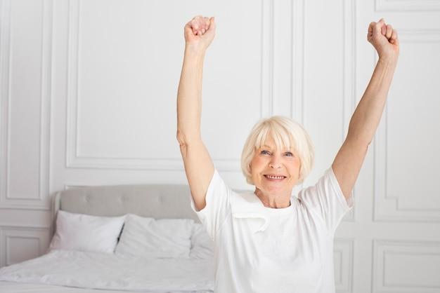 Ältere frau des smiley, die im schlafzimmer sitzt Kostenlose Fotos