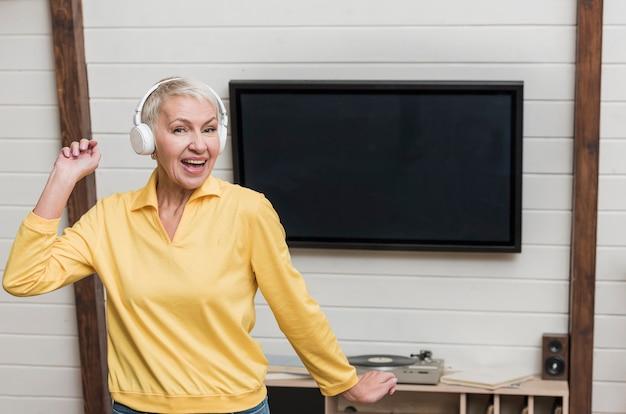 Ältere frau des smiley, die musik durch drahtlose kopfhörer hört Kostenlose Fotos