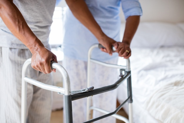 Ältere frau, die älteren mann hilft, mit wanderer zu hause
