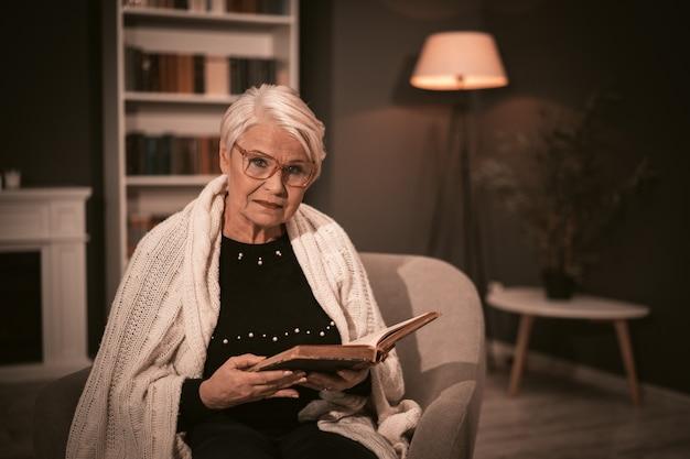 Ältere frau, die altes buch liest, das in einem stuhl sitzt. Premium Fotos