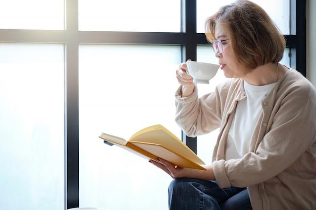 Ältere frau, die am fenster ein buch am entspannenden tag mit einem tasse kaffee liest. Premium Fotos