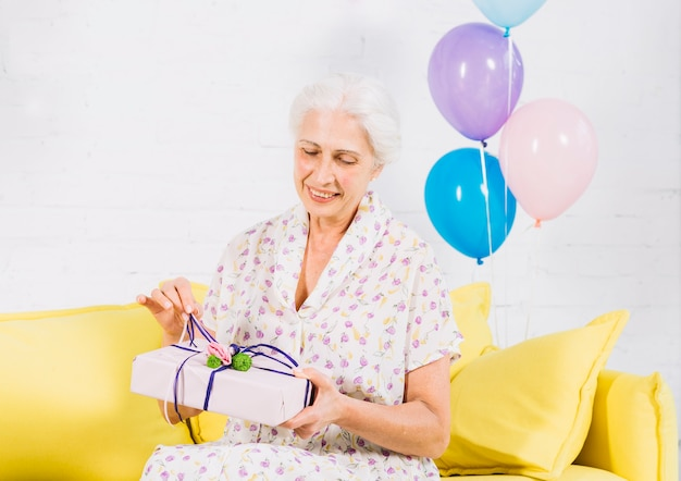 Ältere frau, die auf dem sofa auspackt geburtstagsgeschenk sitzt Kostenlose Fotos