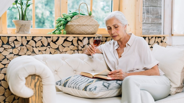 Ältere frau, die auf dem sofa hält weinglas-lesebuch sitzt Kostenlose Fotos