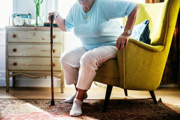 Ältere frau, die auf dem stuhl sitzt Premium Fotos