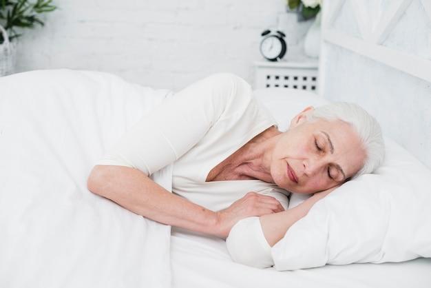 Ältere frau, die auf einem weißen bett schläft Kostenlose Fotos