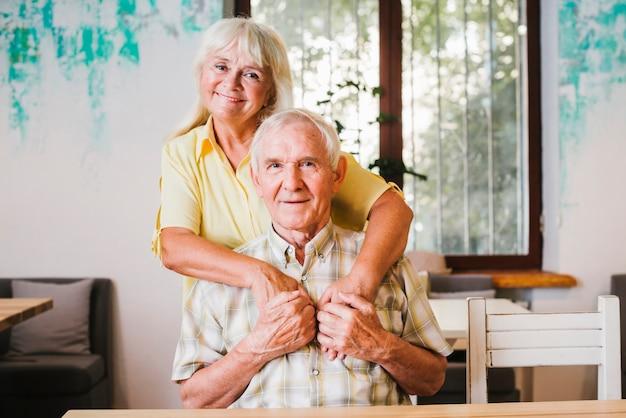 Ältere frau, die den älteren mann zu hause sitzt umfasst Kostenlose Fotos