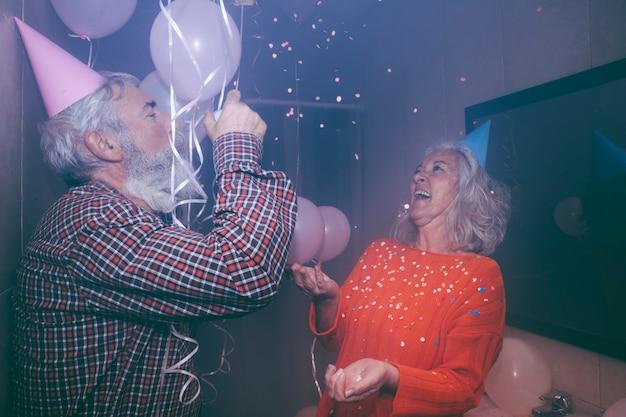 Ältere frau, die die geburtstagsfeier mit ihrem ehemann in der geburtstagsfeier genießt Kostenlose Fotos