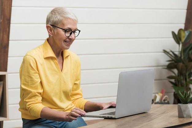 Ältere frau, die durch das internet auf ihrem laptop schaut Kostenlose Fotos
