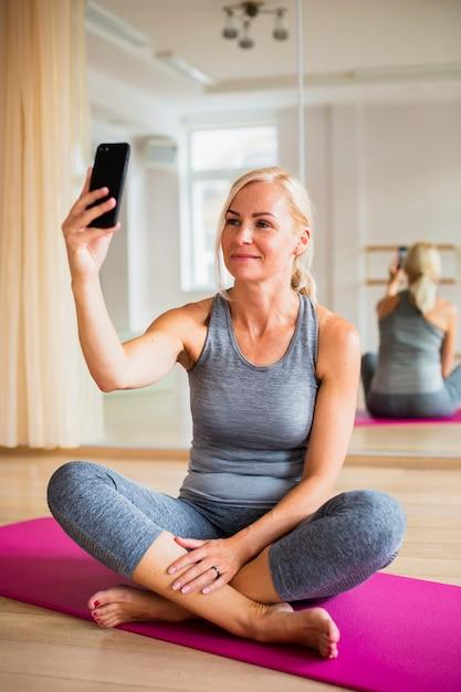 Ältere frau, die ein selfie auf yogamatte nimmt Kostenlose Fotos