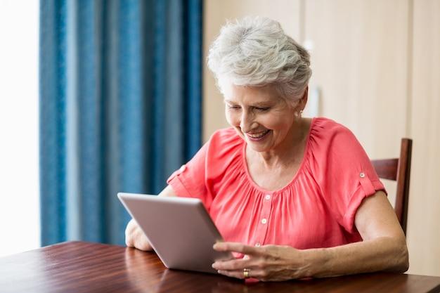 Ältere frau, die eine tablette verwendet Premium Fotos