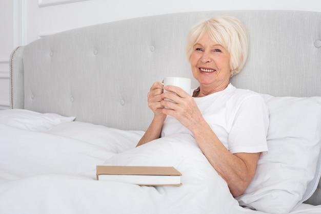 Ältere frau, die eine tasse im schlafzimmer liest Kostenlose Fotos