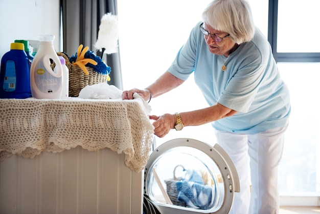 Ältere frau, die eine wäscherei tut Kostenlose Fotos
