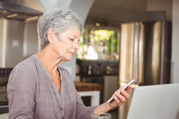Ältere frau, die einen handy anhält Premium Fotos