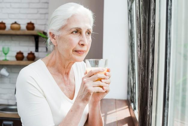 Ältere frau, die einen saft isst Kostenlose Fotos