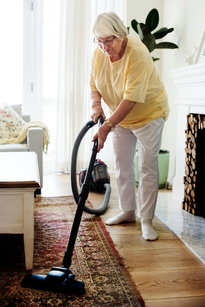 Ältere frau, die einen teppich saugt Premium Fotos
