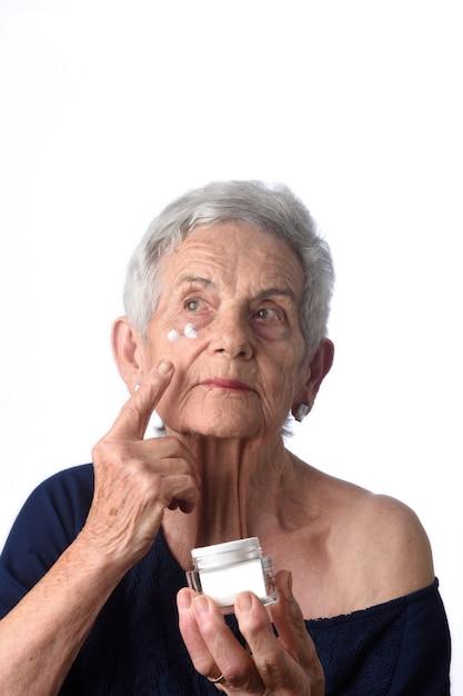 Ältere frau, die hautcreme oder feuchtigkeitscreme an ihrem gesicht aufträgt Premium Fotos