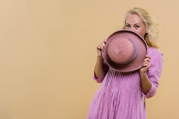 Ältere frau, die ihr gesicht mit einem rosa hut bedeckt Kostenlose Fotos
