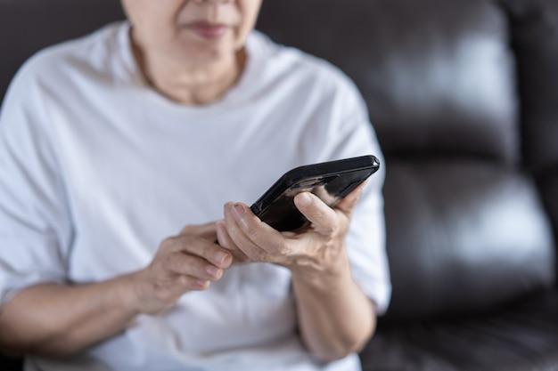 Ältere frau, die ihr telefon im haus verwendet Premium Fotos