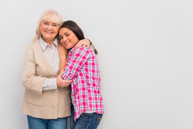 Ältere frau, die ihre junge tochter steht gegen weiße wand umfasst Kostenlose Fotos