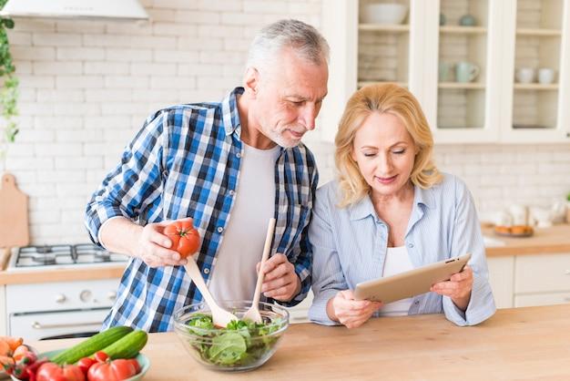 Ältere frau, die ihrem ehemann rezept den salat in der küche zubereitet zeigt Kostenlose Fotos
