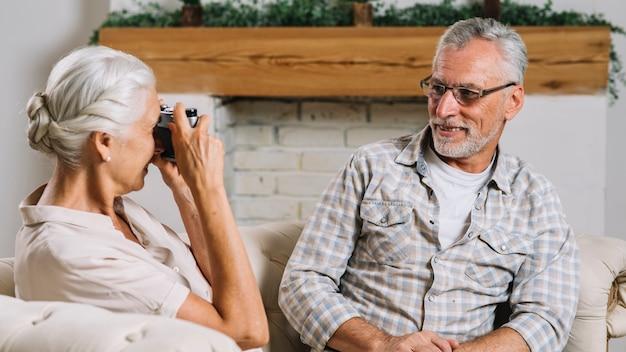 Ältere frau, die ihren lächelnden ehemann mit kamera fotografiert Kostenlose Fotos