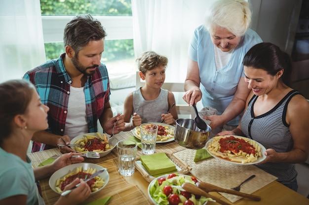 Ältere frau, die ihrer familie mahlzeit serviert Premium Fotos
