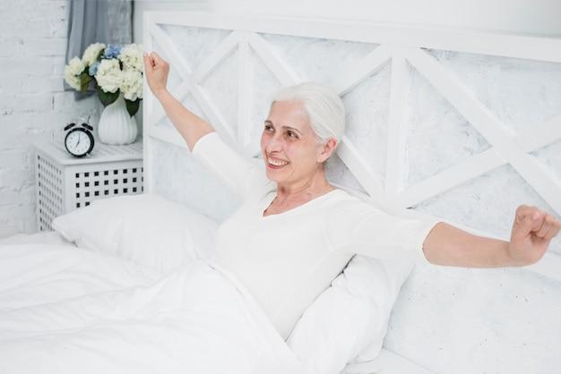 Ältere frau, die im bett aufwacht   Kostenlose Foto