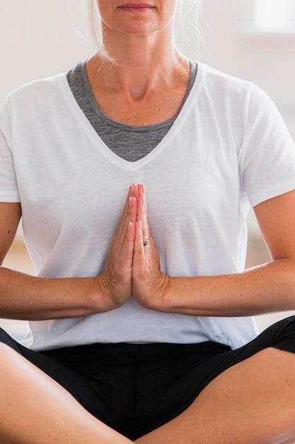 Ältere frau, die meditation ausübt Kostenlose Fotos