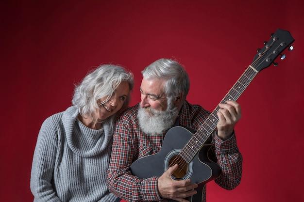 Ältere frau, die nahe ihrem ehemann spielt die gitarre gegen roten hintergrund sitzt Kostenlose Fotos