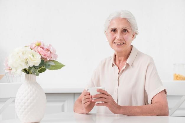 Ältere frau, die tasse kaffee mit blumenvase auf weißer tabelle hält Kostenlose Fotos