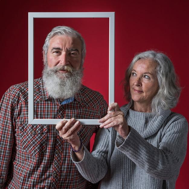 Ältere frau, die weiße rahmengrenze vor gesicht ihres ehemanns gegen roten hintergrund hält Kostenlose Fotos