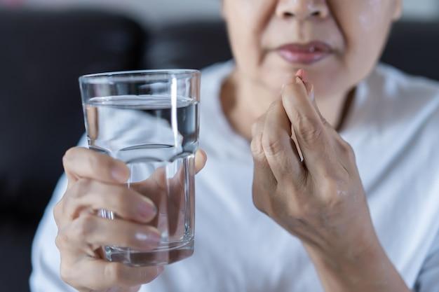 Ältere frau essen droge medizin, die gesunde medizin isst Premium Fotos
