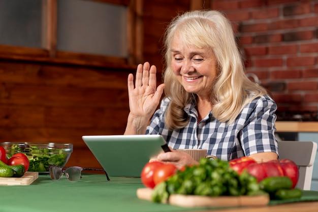 Ältere frau in der küche unter verwendung der tablette Kostenlose Fotos