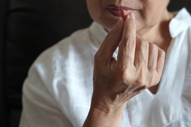 Ältere frau isst medizin und mit pillen und glas wasser zu hause Premium Fotos
