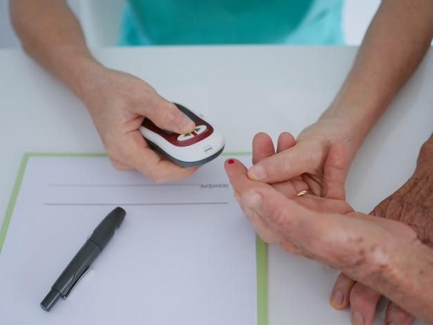 Ältere frau mit bluttests im krankenhaus. Premium Fotos