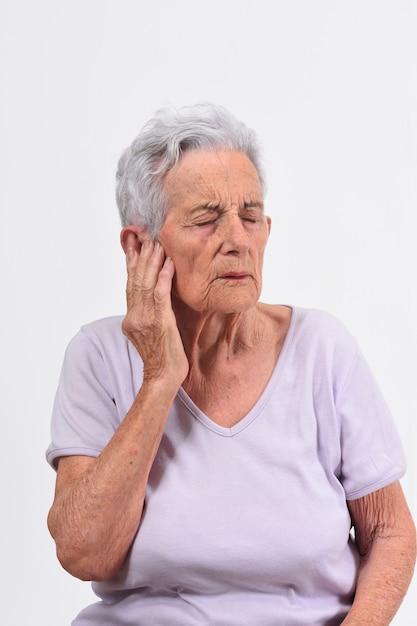 Ältere frau mit den schmerz auf ohr auf weißem hintergrund Premium Fotos