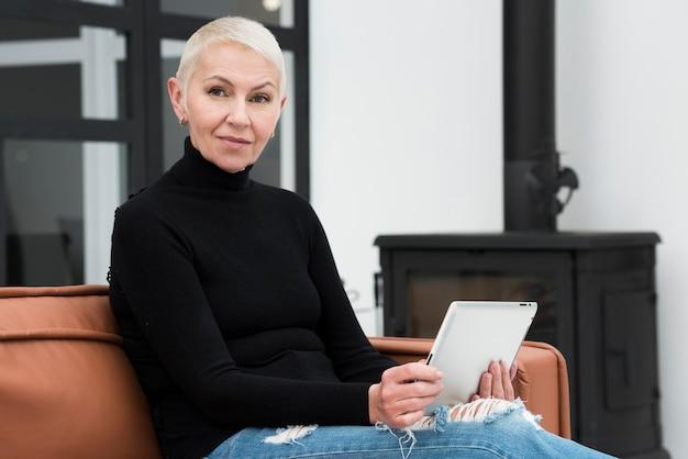 Ältere frau mit der tablette, die auf couch sich entspannt Kostenlose Fotos