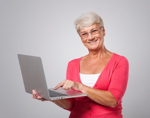 Ältere frau mit zeitgenössischem laptop Kostenlose Fotos