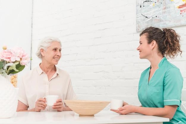 Ältere frau und weibliche krankenschwester, die kaffee zusammen trinkt Kostenlose Fotos