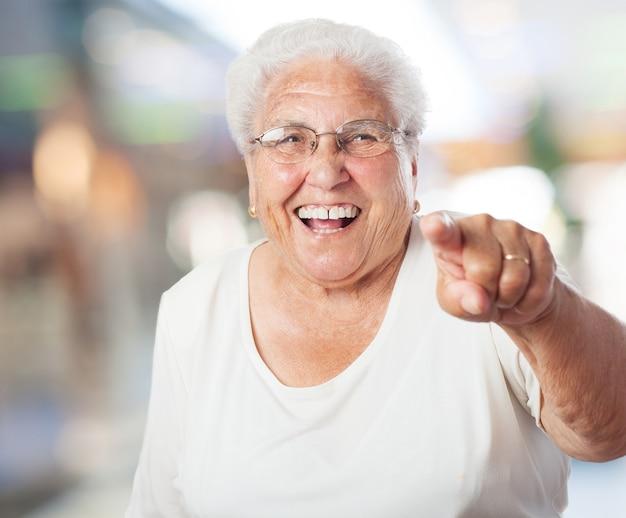 Ältere frau zeigen und lachen Kostenlose Fotos